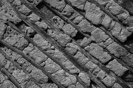 Old stone and wood wall texture background. Vintage black and white