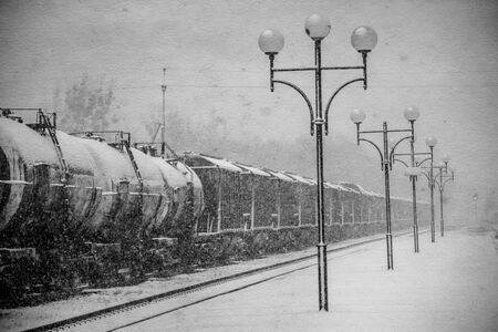 Blizzard on railway, freight train in snow. Vintage black and white