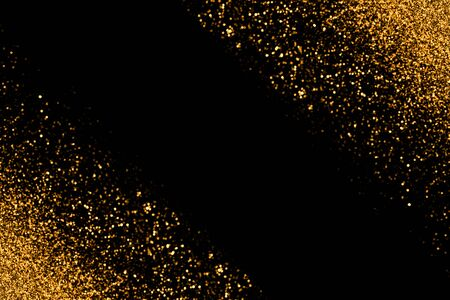 Defocused gold glitter with glowing sparks lights on a black background. Holiday greeting card.
