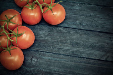 Red cherry tomatoes on blue dark wooden background. Top view. Vintage toned Stock Photo