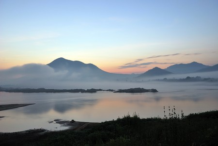 obscured: Light morning with fog obscured the mountains and river. Stock Photo