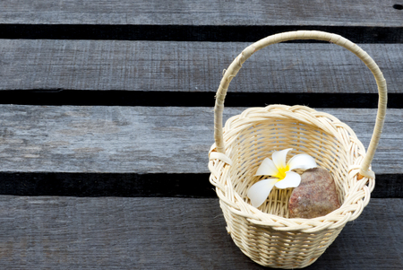 scincare: Beauty spa and fashion concept with spa on rustic wooden background.Frangipani flowers and stone in the wood basket on wooden background
