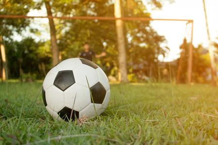 training session: Boy kicking soccer ball on sports field. Soccer football training session for children. Stock Photo