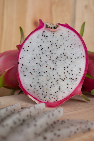 Dragon fruits on wooden background, Sliced delicious dragon fruit on wooden background.