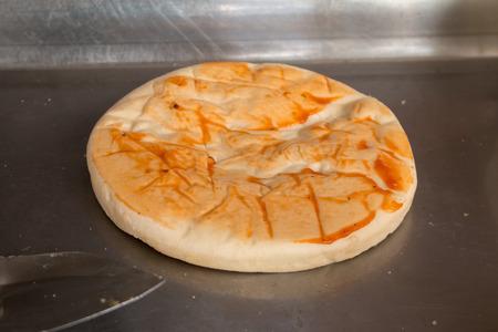 Ingrediënten toevoegen aan zelfgemaakte pizza Stockfoto
