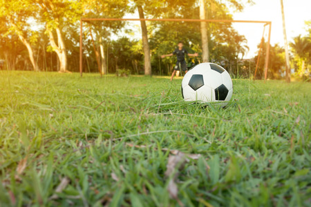 Boy kicking soccer ball on sports field. Soccer football training session for children. Stock Photo