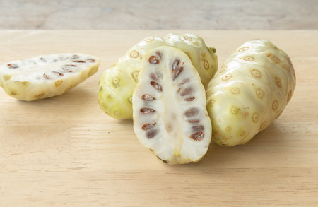 great morinda: Noni or Morinda citrifolia, great morinda, Indian mulberry, beach mulberry, or cheese fruit on wood table. Stock Photo
