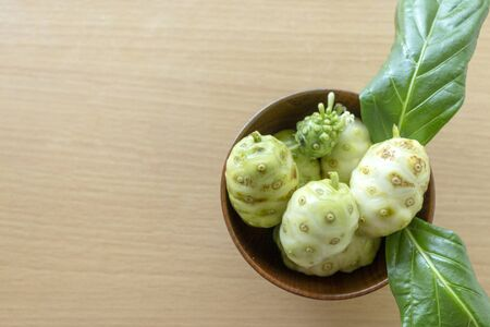 Noni or Morinda citrifolia, great morinda, Indian mulberry, beach mulberry, or cheese fruit on wood table. Stock Photo