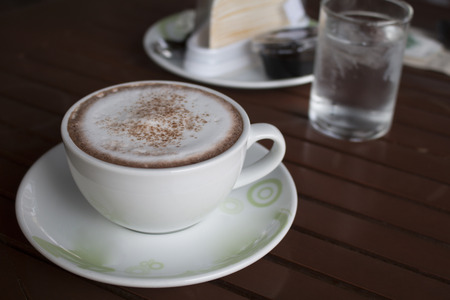 frothy: Closeup of A cup of Latte Art hot coffee over wooden  table. Stock Photo