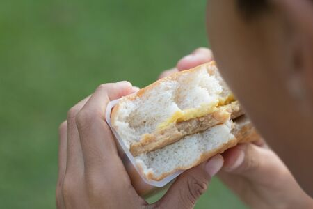 A boy is eating burger with green field background, picnic concept.