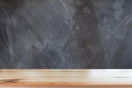 Wooden desk with cement wall texture abstract background.