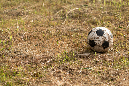 The Old soccer ball on grass worse, Poor soccer game field at countryside. Stock Photo