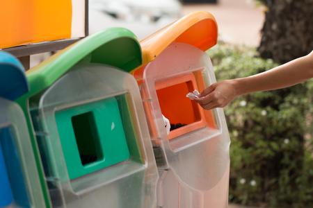 ゴミ箱に紙を置く女性。 写真素材