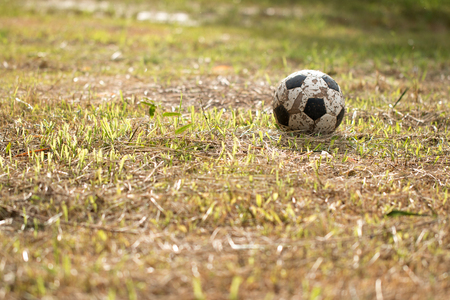 play the old park: The Old soccer ball on grass worse, Poor soccer game field at countryside. Stock Photo