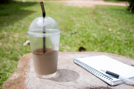 notepaper: After drink ice coffee cup on wooden work desk with notebook and pen, Hard work concept.