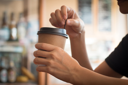 A woman is holding a  coffee cup in coffee's shop at noon.