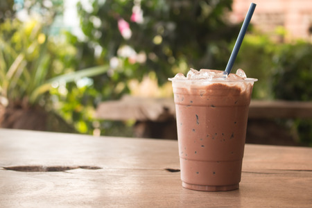 Iced chocolate milkshake, Summer refreshment drinks on wooden background in cafe.