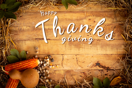 Autumn and Thanksgiving day  background from fallen leaves and fruits with vintage light setting on old wooden table.