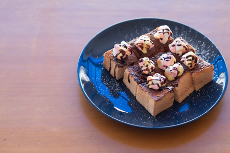 Toasted bread with MARSHMALLOWS topping with chocolate sauce on wooden plate.