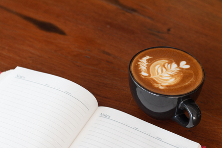 A cup of Piccolo Latte art  on wooden desk, Relaxing time or coffee's break time during work day.