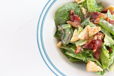 Closeup of healthy Caesar salad with croutons and Ham sliced.