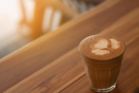 Piccolo Latte art in small glass on wooden desk.