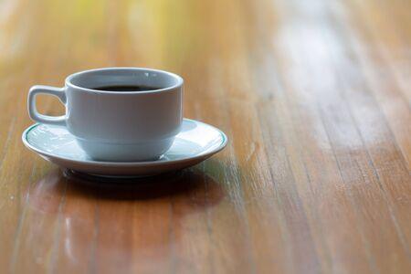 Zamknąć filiżankę gorącej kawy na drewnianym stole.