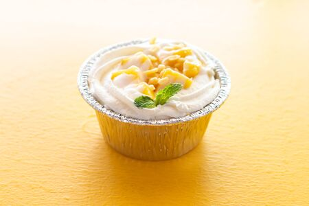 Summer fruit dessert is Mango cheesecake on yellow table background.