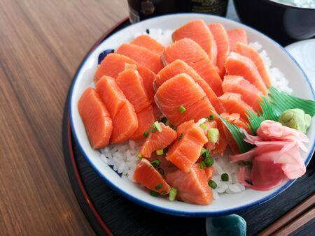 Shalmon Sashimi in dish on wooden table.