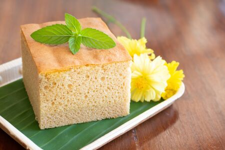 Homemade sponge cake on wooden plate decorate with cute yellow flower in coffee's shop.