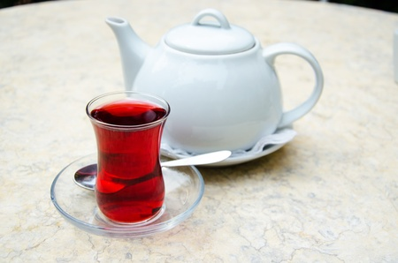 Traditional turkish glass of fruit tea and white ceramic teapot photo