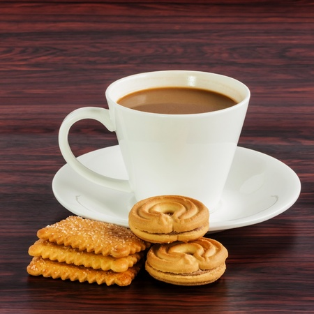 Coffee cup and cookies on wooden table photo
