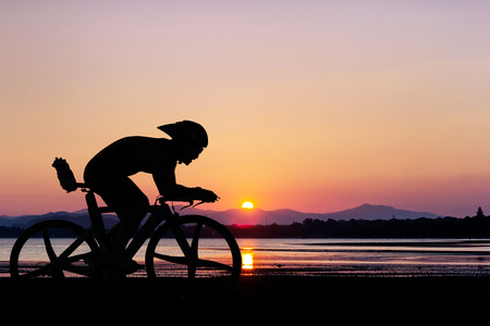 Cycling at black mountain and beach on twilight Stok Fotoğraf