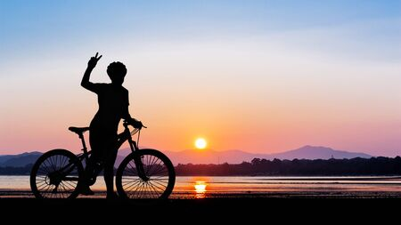 cycling silhouette: Women cycling at clean beauty beach on twilight time in Thailand