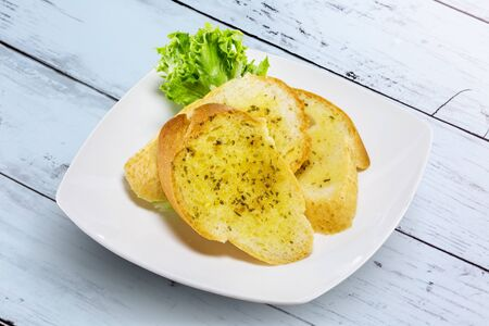 Garlic bread with white plate on wooden table