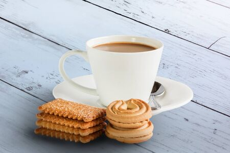 Cup of coffee and cookie on wooden table