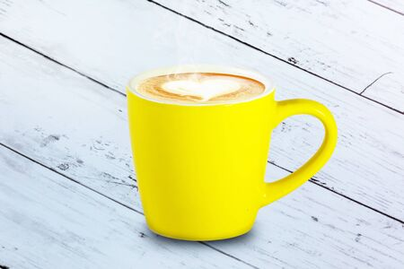 Coffee yellow cup on wooden table Imagens