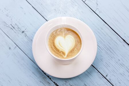 Coffee love cup on wooden table Imagens