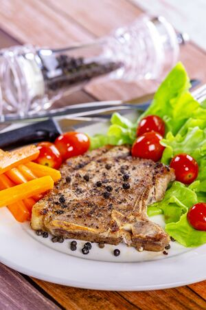 Pork steak white plate on wooden table Фото со стока