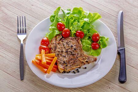 Pork steak white plate on wooden table Stok Fotoğraf