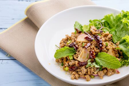 Spicy minced pork salad on wooden table