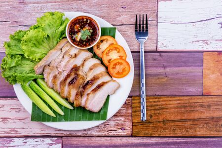 Grilled pork slice on white plate wooden table