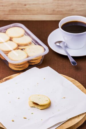 Crackers with black coffee on wooden table