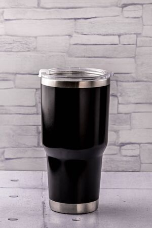 Thermo bottle black colour container on gray background Standard-Bild
