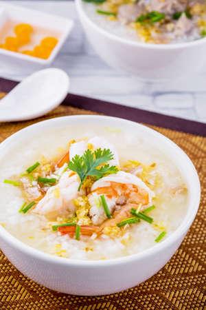 Shrimp porridge white bowl isolate on wooden background Archivio Fotografico