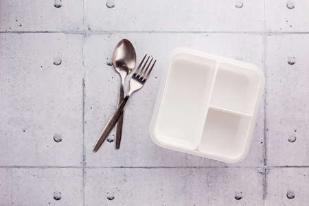 Empty white plastic food container with spoon and fork on wooden table Stock fotó