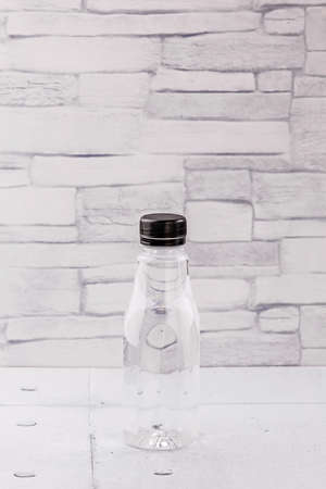 Water plastic bottle on gray wooden background
