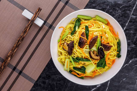 Fried vegetarian shou noodles Asia cuisine on dark wooden background 版權商用圖片