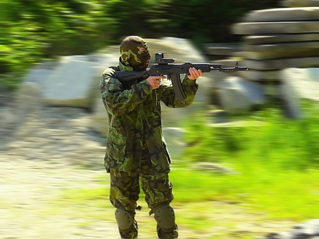 robustness: airsoft boy with ak47, hard motion blur background