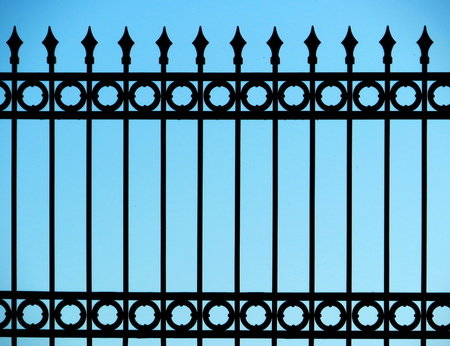 Old and rusty wrought iron fence on blue sky